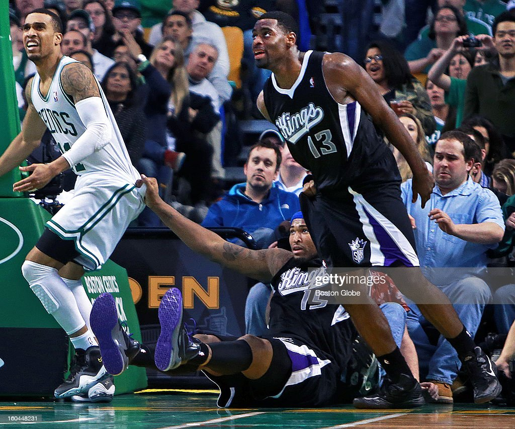 The Kings' DeMarcus Cousins tries to soften his landing by using the shorts of the Celtics' Courtney Lee, left, as well as his teammate Tyreke Evans, right, as he was hitting the floor during a fourth quarter play along the baseline as the Boston Celtics hosted the Sacramento Kings in an NBA regular season game at the TD Garden.