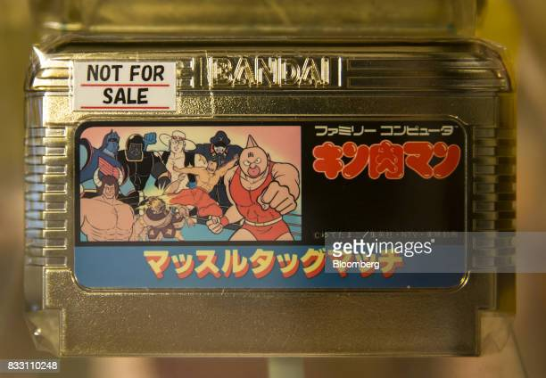 The Kinnikuman Muscle Tag Match gold version video game cartridge for the Nintendo Co Nintendo Entertainment System /Famicom console is displayed at...