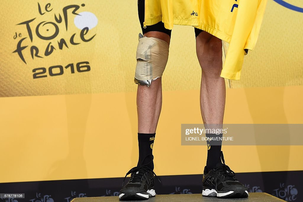 The knee injured of Great Britain's Christopher Froome is pictured as Froome celebrates his overall leader yellow jersey on the podium at the end of the 146 km nineteenth stage of the 103rd edition of the Tour de France cycling race on July 22, 2016 between Albertville and Saint-Gervais Mont Blanc, French Alps. BONAVENTURE