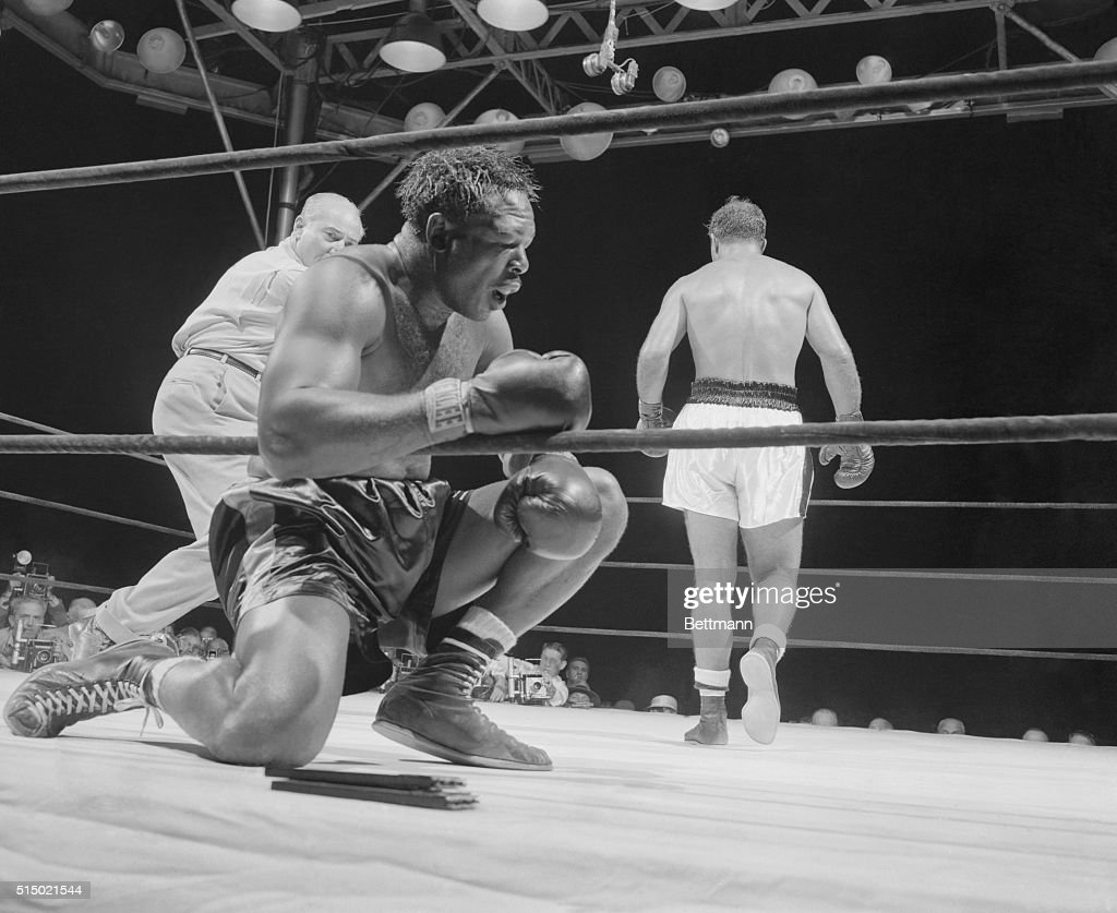 The Knees Buckled Under Old Arch. New York, New York: Rocky Marciano backs away from the floored <a gi-track='captionPersonalityLinkClicked' href=/galleries/search?phrase=Archie+Moore&family=editorial&specificpeople=93092 ng-click='$event.stopPropagation()'>Archie Moore</a> in the ninth and final round of their title bout at the stadium tonight. The knees literally buckled under the game challenger after he absorbed a flurry of lefts and rights. He is down for the count. Time was 1:19.