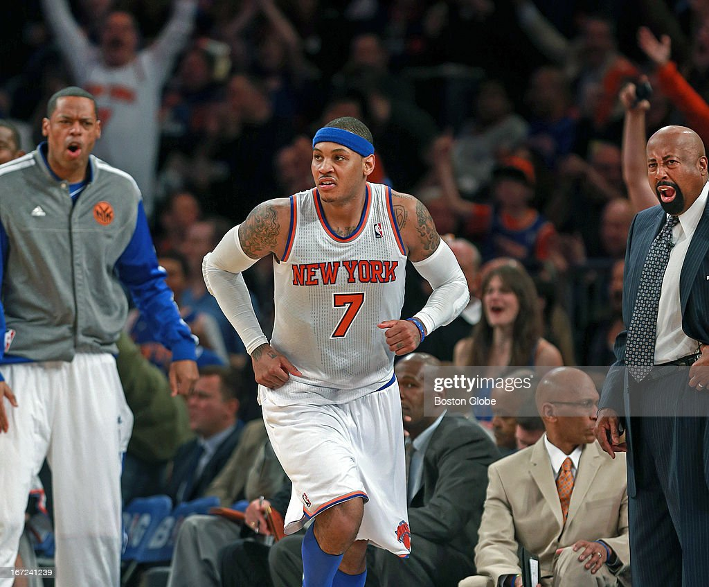 The Knicks Carmelo Anthony (#7) brings the fans, teammate Marcus Camby, left, and head coach Mike Wodson, right, out of their seats after hitting a long ball in the first half. The Boston Celtics visited the New York Knicks in Game One of an NBA Eastern Conference Quarterfinal Playoff game at Madison Square Garden.