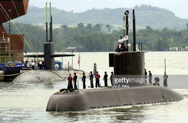 The Korean submarine Choi Moo Sun makes its way past the US Navy's USS Helena during 'Exercise Pacific Reach' September 28 2000 in the Sembawang port...