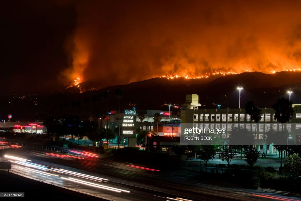 The La Tuna Canyon fire burns in the hills above Burbank, California, early September 2, 2017. The brush fire which quickly burned 2,000 acres started on September 1 and was being driven by heat wave temperatures and high winds. / AFP PHOTO / Robyn Beck