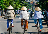The ladies riding bikes in conical hats