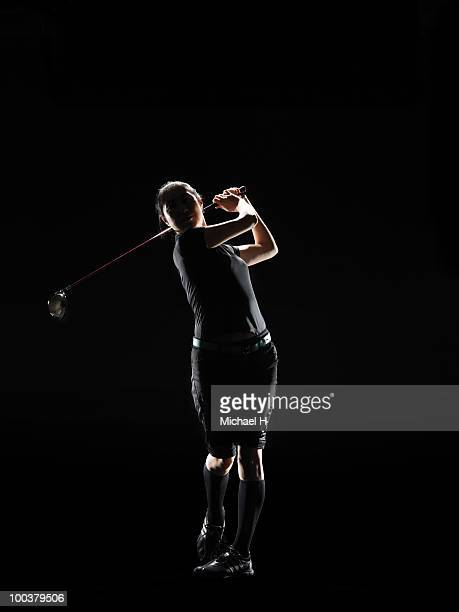 The lady golfer swings the driver of golf