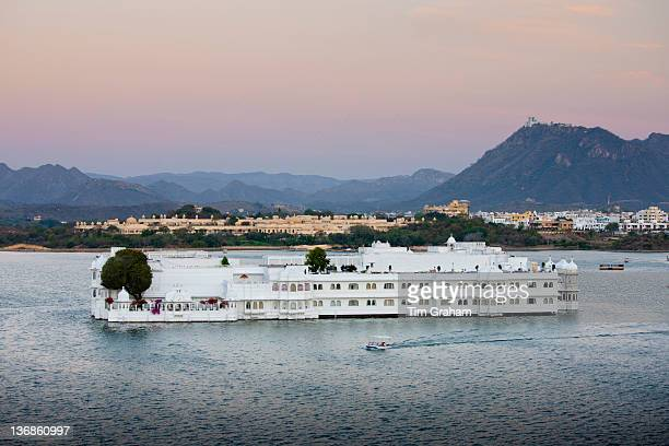 The Lake Palace Hotel Jag Niwas on island site on Lake Pichola in early morning with tourist boat leaving Udaipur Rajasthan India