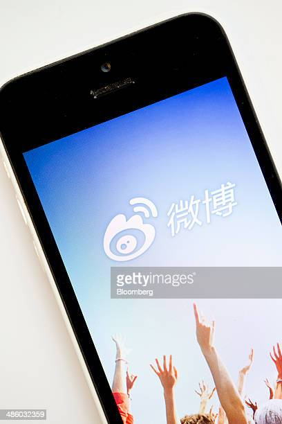 The landing page for Sina Corp's Sina Weibo microblogging service app is displayed on an Apple Inc iPhone 5s in an arranged photograph in Hong Kong...