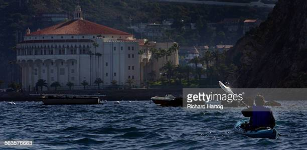 The landmark casino can be seen in the backround as a lone man paddles a kayak in the waters Monday morning at Catalina Island @@*Note – the man in...