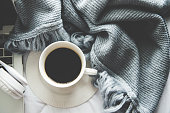 The laptop working and listen music on the white bed and coffee with marshmallow, warm knitted sweater in the sunny day.  Cozy winter home morning holiday.  Music and Lifestyle Concept.