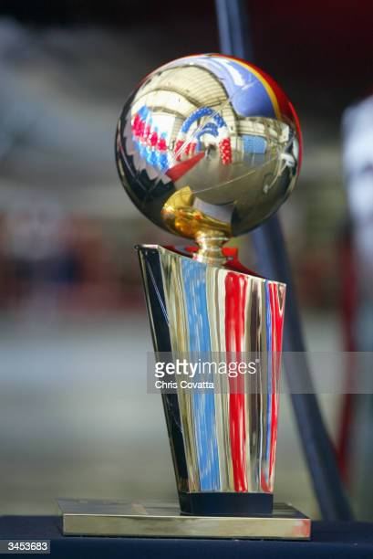 The Larry O'Brien trophy rests on a table with the reflection of red white and blue balloons showing in the airport hanger during the NBA Legends...