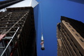 The last 75foot section of the 408foot spire is viewed as it is hoisted onto a temporary platform on the top of One World Trade Center on May 2 2013...