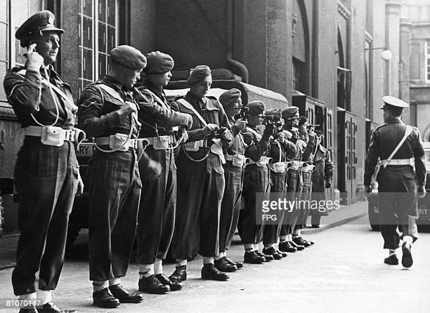 The last guard of the British Military Police officers present their unloaded pistols in the courtyard of the Hamburg Curio Haus after the last of...