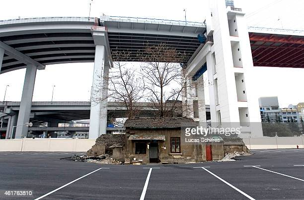 The last house of an old neighborhood stands alone in a future Shanghai World Expo 2010 parking lot under Nanpu bridge on April 6 2010 in Shanghai...