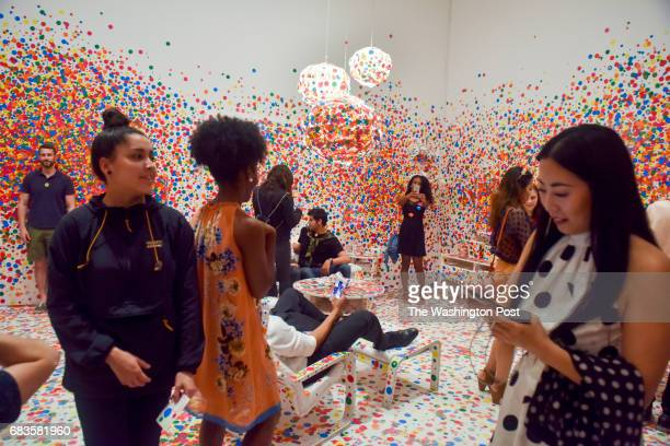 The last wave of visitors applies the final dots to the Obliteration Room on the final day of the Yayoi Kusama Infinity Mirrors exhibit at the...
