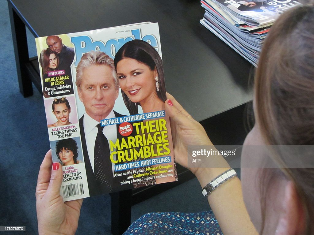 The latest issue of People magazine is seen in Los Angeles on Auggust 28, 2013. Hollywood A-listers Michael Douglas and Catherine Zeta-Jones, one of Tinseltown's most high-profile couples, have decided to take a break from their 13-year marriage, representatives for the pair said Wednesday. The 68-year-old US actor and his 43-year-old British wife have two children, Dylan, 13, and 10-year-old Carys -- and decided to live apart after Douglas returned from the Cannes Film Festival in May, shortly after his wife checked in for a second round of treatment for bipolar disorder, People magazine reported. 'Michael and Catherine are taking some time apart to evaluate and work on their marriage. There is no further comment,' Douglas spokesman Allen Burry told AFP, confirming the cover story in the latest issue of People. AFP PHOTO/Michael THURSTON