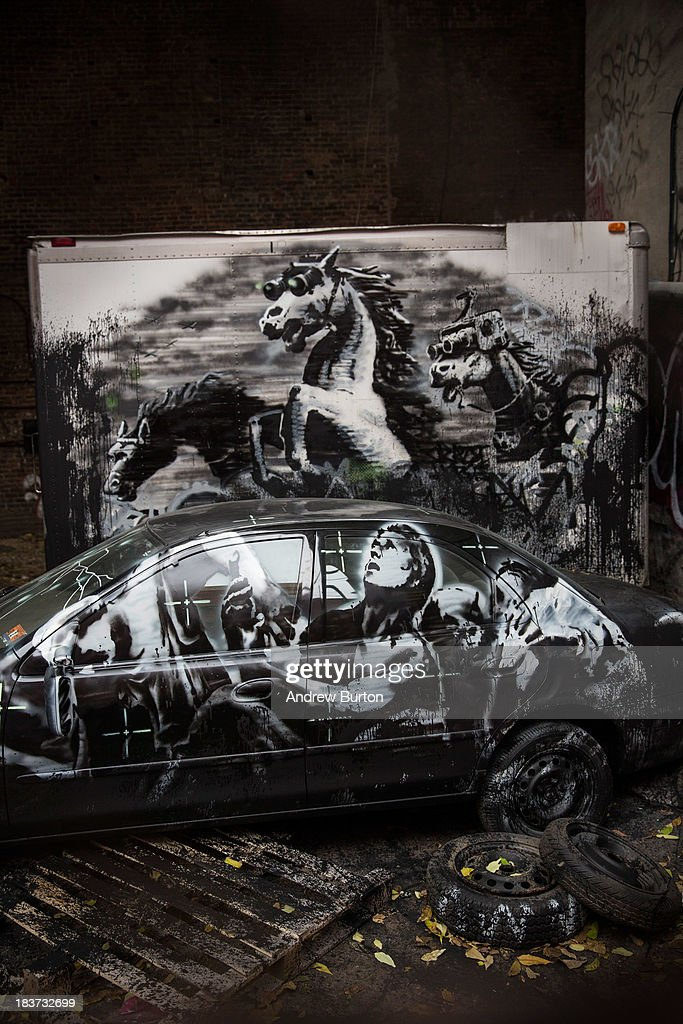 The latest work from street artist Banksy is seen through a chain link fence on October 9, 2013 in the Lower East Side neighborhood of New York City. Banksy is in the midst of creating a month long series of pieces of street art.