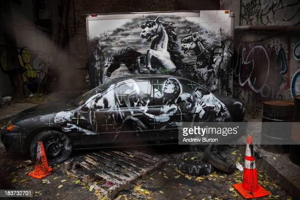 The latest work from street artist Banksy is seen through a chain link fence on October 9 2013 in the Lower East Side neighborhood of New York City...