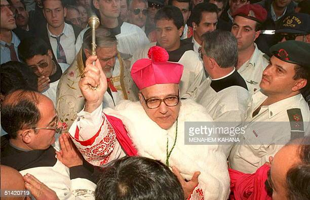 The Latin Patriach of Jerusalem Michel Sabbah sprinkles holy water on the crowd before he enters the Church of Nativity in Bethlehem 24 December...