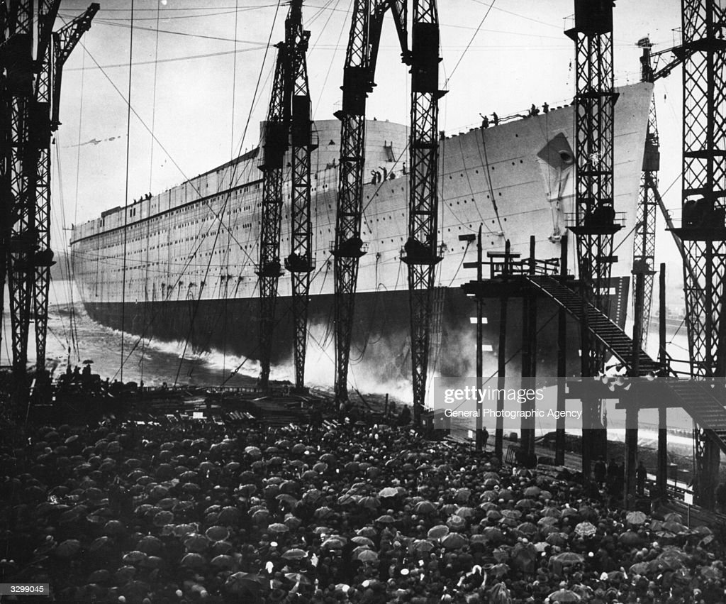 The launching of the liner 'Queen Mary' seen through the cranes along the dock and over the heads of a packed crowd.