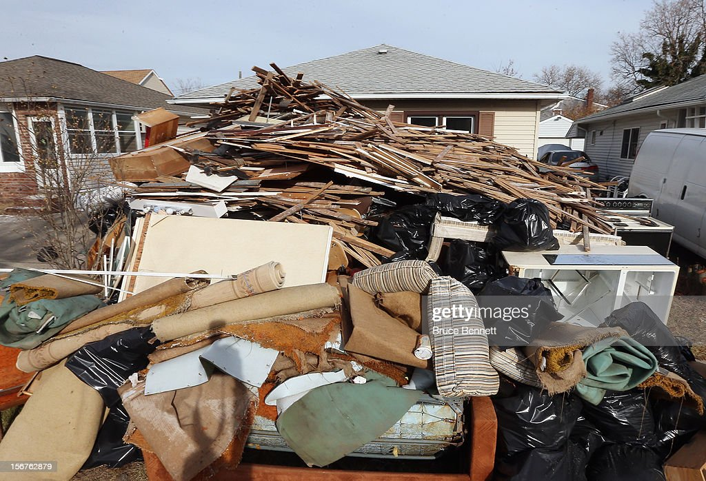 The lawn in front of a home on East Harrison is piled high with debris on November 20, 2012 in Long Beach, New York. More than three weeks after Superstorm Sandy hit the New York area, residents continue their restoration efforts in many affected areas on Long Island.