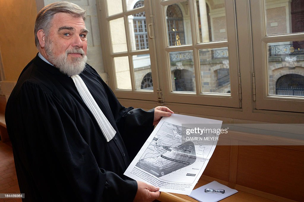 The lawyer for Lemacon's widow Chloe, Arnaud Colon de Franciosi holds a document on October 14, 2013 at Rennes' courthouse, prior to the opening hearing of the pirates' trial for hijacking a yacht in 2009. French troops stormed the Tanit sailboat on April 10, 2009 and captured the trio in a bid to free Florent Lemacon, his wife, their three-year-old son and two others. AFP PHOTO/ DAMIEN MEYER