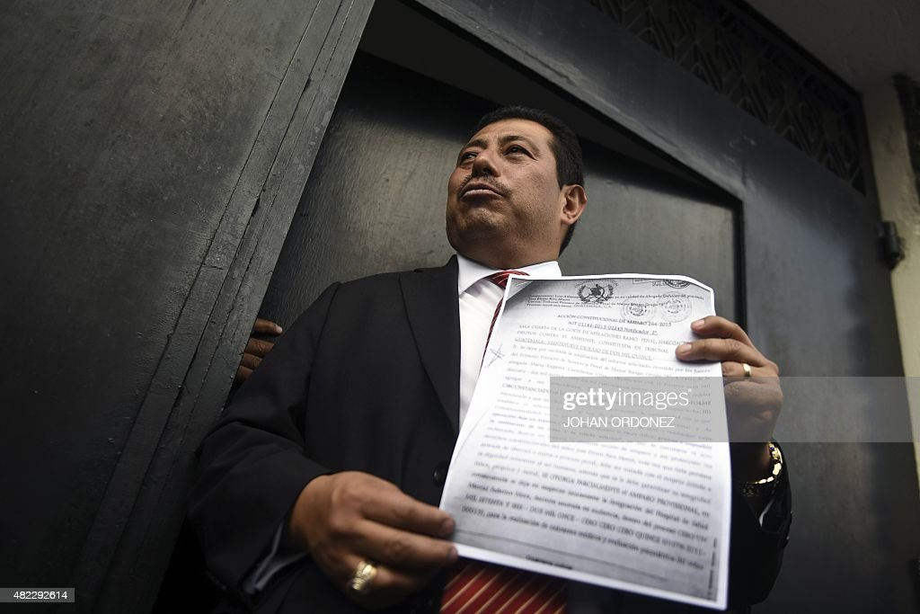 The lawyer of former Guatemalan dictator Jose Efrain Rios Montt Jaime Hernandez shows to journalists the document explaining the legal protection...