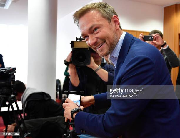 The leader of Germany's free democratic FDP party Christian Lindner mounts a cell phone to stream his press conference he gave on his latest book...