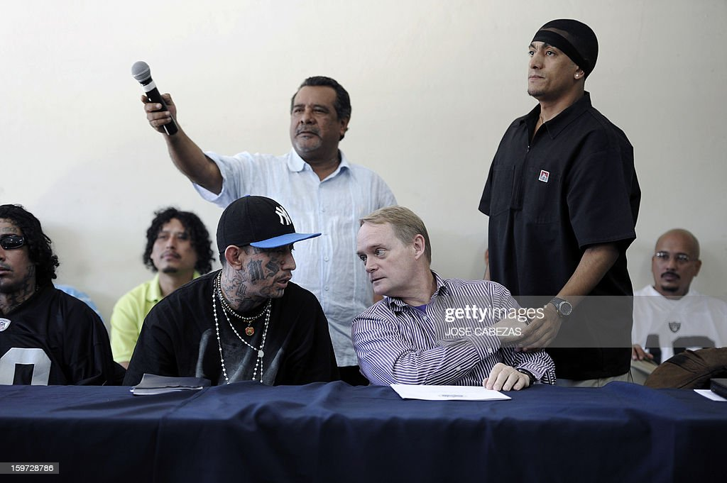 The leader of the Mara Salvatrucha gang, Carlos Alberto Valladares (C-L), speaks with the Secretary of Multidimensional Security at the Organization of American States (OAS) Adam Blackwell(C-R) during a press conference at La Esperanza Penitenciary in San Salvador, El Salvador on January 19, 2013. Leaders of Salvadorean MS-13, 18th street, Mara Maquina and Mao-Mao gangs participated in a press conference during a campaign to reduce crime in El Salvador. AFP PHOTO/ Jose CABEZAS