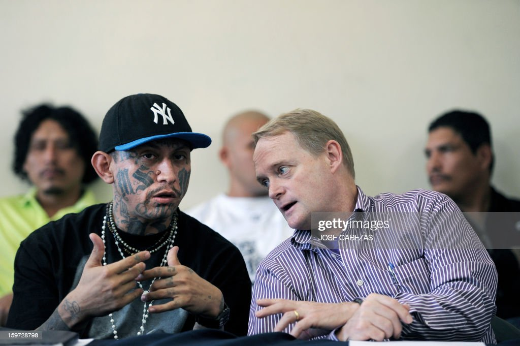 The leader of the Mara Salvatrucha gang, Carlos Alberto Valladares (L), speaks with the Secretary of Multidimensional Security at the Organization of American States (OAS) Adam Blackwell during a press conference at La Esperanza Penitenciary in San Salvador, El Salvador on January 19, 2013. Leaders of Salvadorean MS-13, 18th street, Mara Maquina and Mao-Mao gangs participated in a press conference during a campaign to reduce crime in El Salvador. AFP PHOTO/ Jose CABEZAS