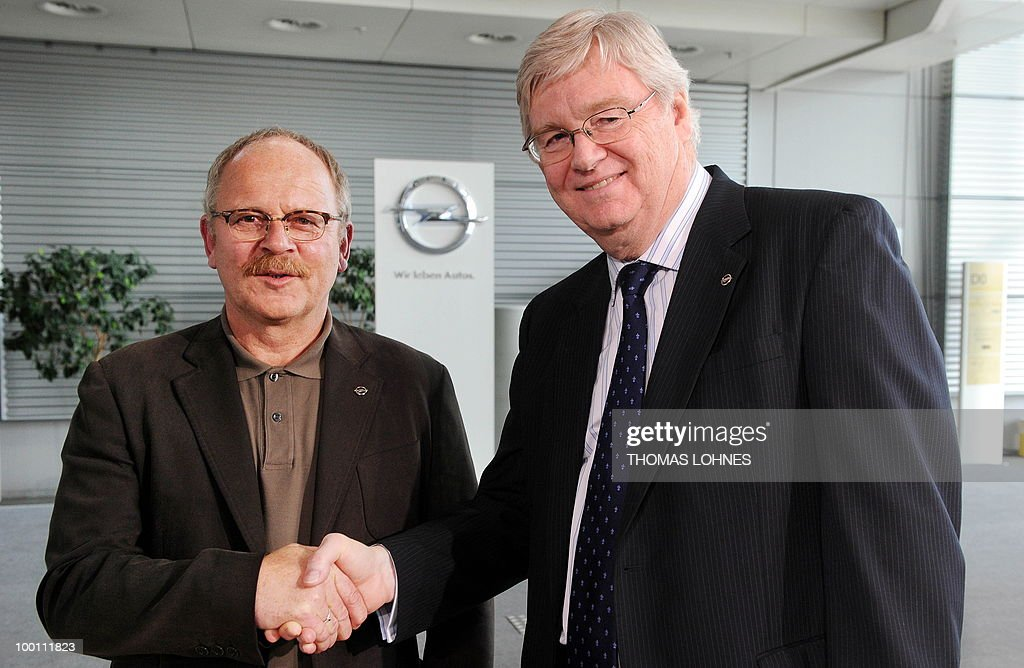 The leader of the Opel works council Klaus Franz (L) and the CEO of Opel, Nick Reilly shake hands at the Opel plant in the central German city of Ruesselsheim on May 21, 2010. General Motors' European unit Opel and unions have agreed on terms of a long-awaited restructuring plan, knocking the ball back into Berlin's court, with GM hoping for financial guarantees in return.
