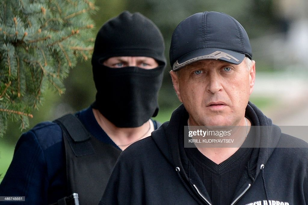 The leader of the separatist rebels in the eastern Ukrainian city of Slavyansk, Vyacheslav Ponomaryov (R) arrives to attend a press-conference in Slavyansk on April 20, 2014. Pro-Moscow rebels in the east Ukraine town of Slavyansk declared a curfew there Sunday, after a gun battle with unidentified attackers killed two militants. Ponomaryov told reporters that 'the curfew comes into effect today'. AFP PHOTO / KIRILL KUDRYAVTSEV