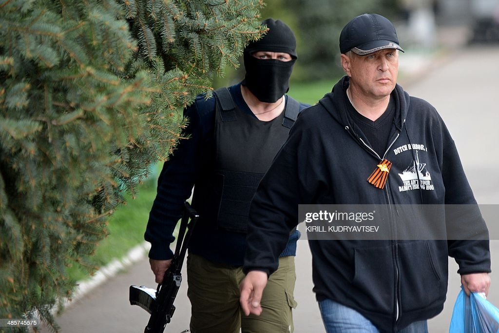 The leader of the separatist rebels in the eastern Ukrainian city of Slavyansk, Vyacheslav Ponomaryov (R), escorted by an armed man, arrives to attend a press-conference in Slavyansk on April 20, 2014. Pro-Moscow rebels in the east Ukraine town of Slavyansk declared a curfew there Sunday, after a gun battle with unidentified attackers killed two militants. Ponomaryov told reporters that 'the curfew comes into effect today'.