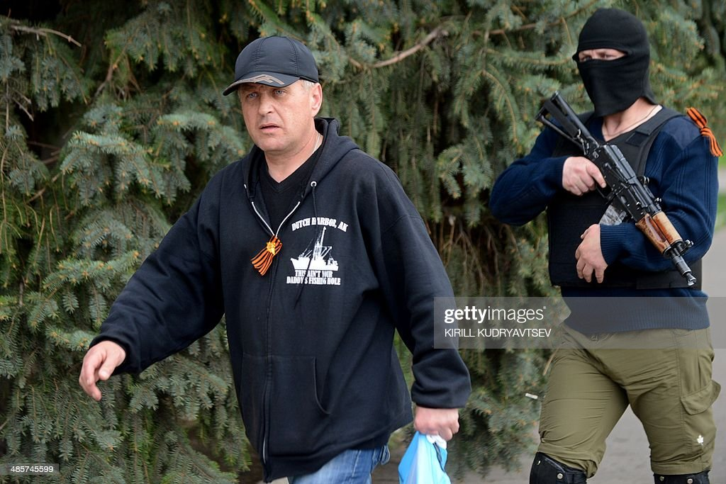 The leader of the separatist rebels in the eastern Ukrainian city of Slavyansk, Vyacheslav Ponomaryov (L), escorted by an armed man, arrives to attend a press-conference in Slavyansk on April 20, 2014. Pro-Moscow rebels in the east Ukraine town of Slavyansk declared a curfew there Sunday, after a gun battle with unidentified attackers killed two militants. Ponomaryov told reporters that 'the curfew comes into effect today'.