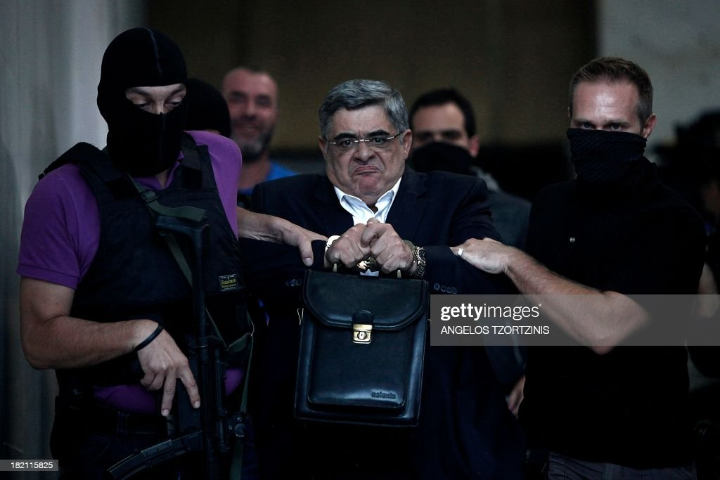 The leader of ultra-right wing Golden Dawn party Nikos Michaloliakos is escorted by masked police officers to the prosecutor from the police headquarters in Athens on September 28, 2013. Greek police on Saturday swooped on the neo-Nazi Golden Dawn party, arresting its leadership and hunting for dozens of members across the country in a crackdown sparked by the murder of a leftist musician. The arrests came a day after Golden Dawn threatened to pull its lawmakers out of parliament, a move that could spark a political crisis in the recession-hit country. AFP PHOTO / Angelos Tzortzinis