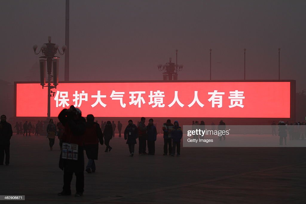 The LED screen shows the slogan 'protecting atmospheric environment is everyone's responsibility' on the Tiananmen Square which is shrouded with heavy smog on January 16, 2014 in Beijing, China. Beijing Municipal Government issued a yellow smog alert this morning.