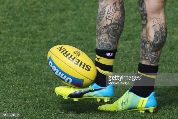 The leg tattoos are seen on Dustin Martin of the Tigers as he kicks the ball during a Richmond Tigers AFL training session at Punt Road Oval on...