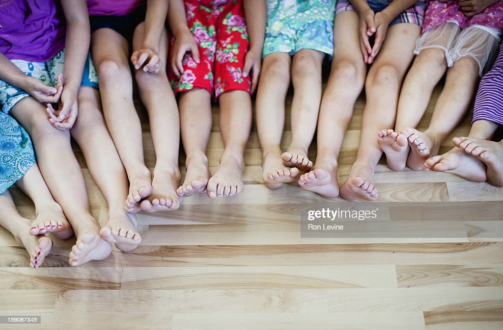 The legs and feet of eight girls sitting : Stock Photo