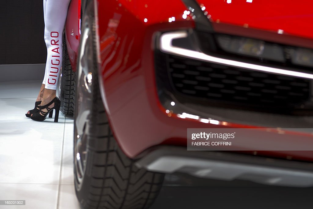 The legs of a model are seen at the booth of Italian car maker Giugiario at the Geneva International Motor Show on March 6, 2013. Global sales of cars, buses, utility vehicles and trucks are expected to grow three percent this year, down from five percent in 2012, according to a forecast published on March 6, 2013. The growth forecast, presented by the International Organisation of Motor Vehicle Manufacturers (OICA) at the Geneva Motor Show, is based on figures provided by the national car federations in three quarters of OICA member countries. AFP PHOTO / FABRICE COFFRINI