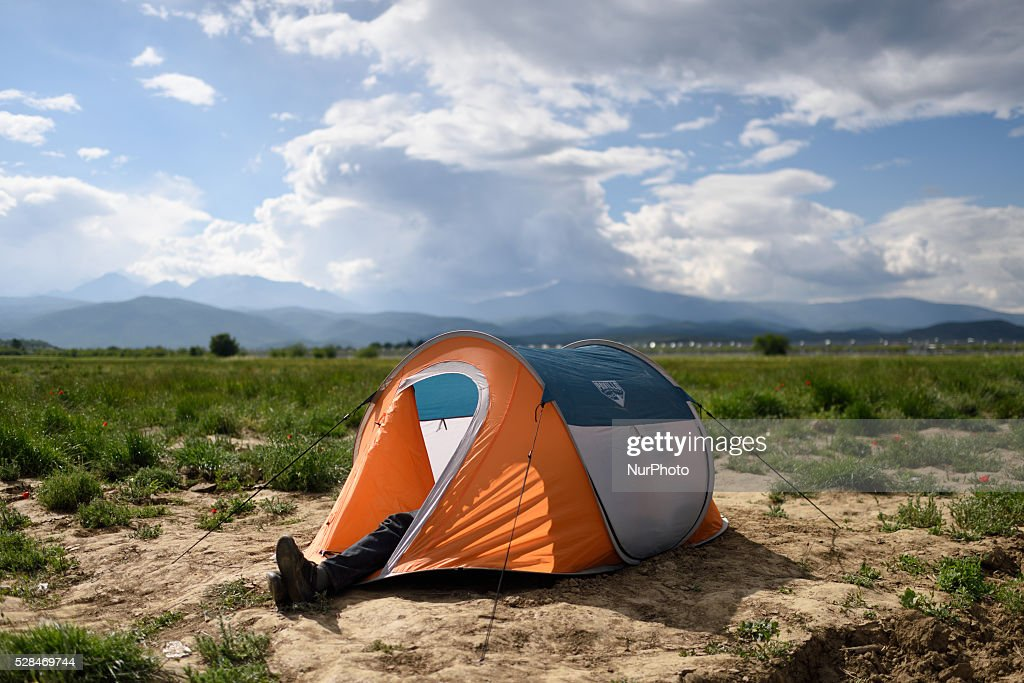 The legs of a refugee are seen out of his tent as he rests inside the tent in a field just next to Idomeni refugee camp on May 5'th, 2016. Thousands of migrants are still located in the makeshift refugee camp, located at the Greek Macedonian border, waiting for the border to re-open.