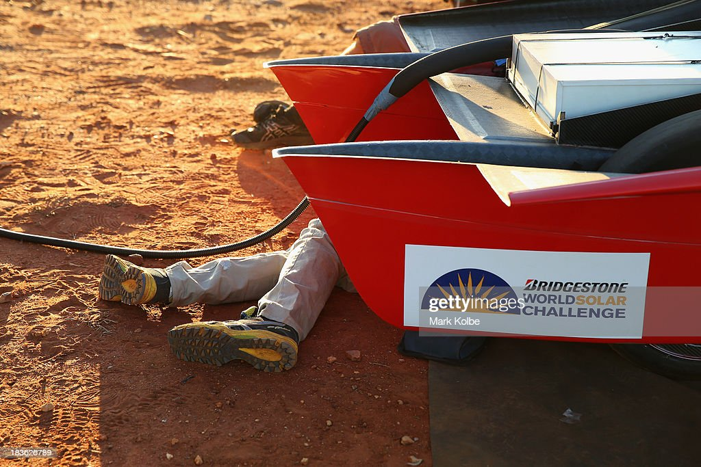 The legs of a team member are seen as he prepares the RED Engine from the Solar Team Twente, University of Twente and Saxion in the Netherlands for the start of racing on Day 3 on October 8, 2013 outside of Ti Tree, Australia. Over 25 teams from across the globe are competing in the 2013 World Solar Challenge - a 3000 km solar-powered vehicle race between Darwin and Adelaide. The race began on October 6th with the first car expected to cross the finish line on October 10th.