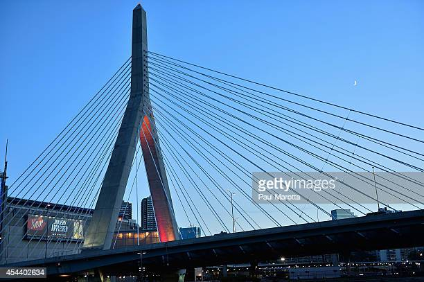 The Leonard P Zakim Bunker Hill Memorial Bridge lights up in support of Stand Up To Cancer at sunset with a crescent moon on August 30 2014 in Boston...