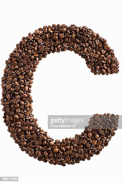 The letter 'C' written in coffee beans on white background, close-up
