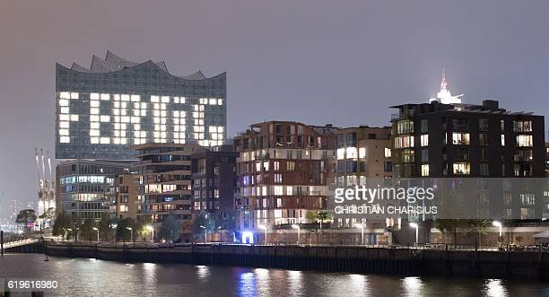 The lettering 'Finished' illuminates the facade of the just completed building of the Elbphilharmonie concert hall in Hamburg northern Germany on...