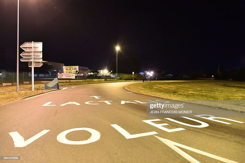 The lettering 'Lactalis Thieves' is seen on street leading towards the Lactalis group headquarters in Change near Laval northwestern France as part...