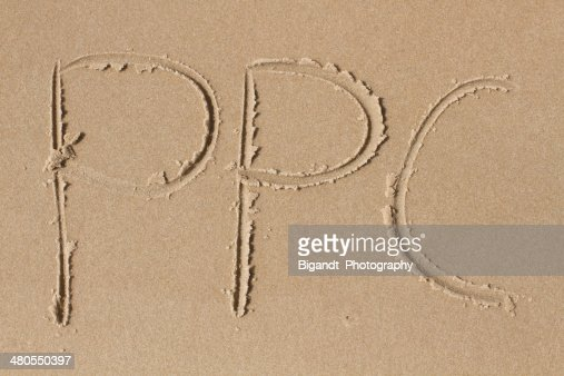 The letters PPC drawn in sand : Stock Photo