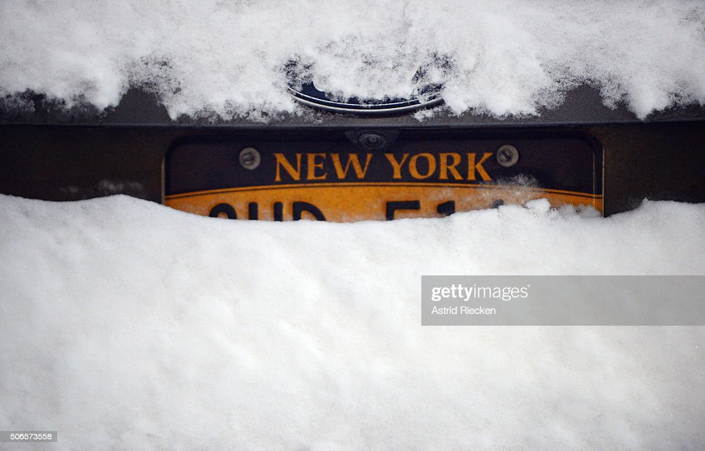 The license plate of a car parked in the Upper West is buried in snow January 24 2016 in New York City People began to dig out after a blizzard...