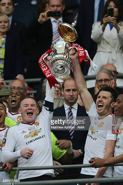 LONDON ENGLAND MAY 21 The lid of the FA Cup Trophy comes off as Wayne Rooney and Michael Carrick lift it during the trophy presentation after The...