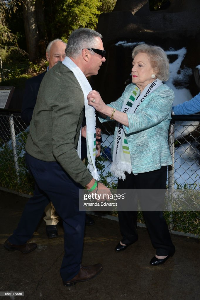 The Lifeline Program spokesperson Betty White (R) adjusts publicist Phil Lobel's scarf at the 'White Hot' Holiday Event at The Los Angeles Zoo on December 11, 2012 in Los Angeles, California.