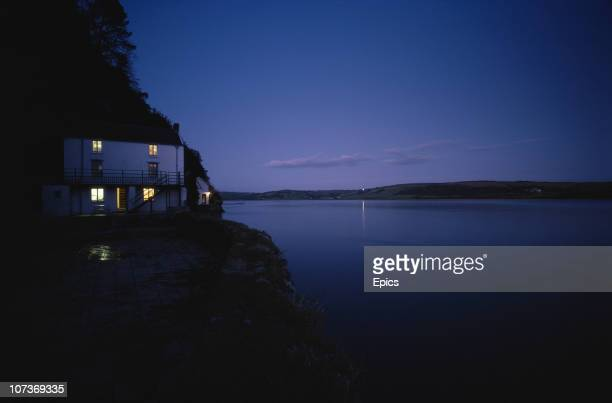 The lights from the windows light up the Dylan Thomas boathouse at dusk Laugharne Carmarthenshire Wales October 1982 The boathouse was the poets home...