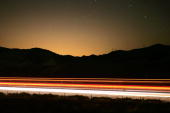 The lights of Los Angeles illuminate the sky behind traffic crossing Tejon Pass near the San Andreas Fault on the main corridor between Los Angeles...